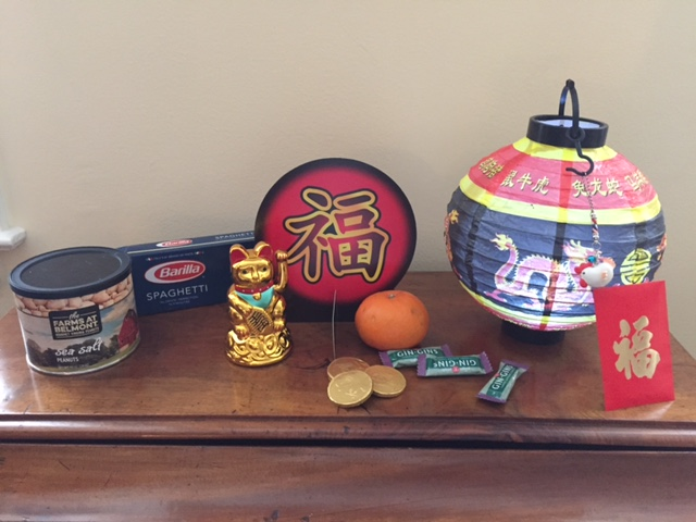 Lucky cat, lantern, rooster charm, chocolate coins, red envelope, new year symbol, peanuts, spaghetti (long noodles) tangerine, ginger chews